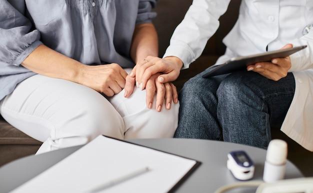 Doctora del centro de recuperación de covid comprobando los resultados de salud con un paciente mayor