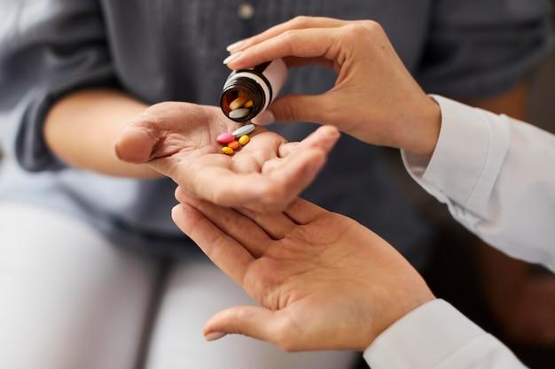 Doctora del centro de recuperación de covid dando pastillas para pacientes mayores de botella en mano
