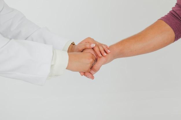 Doctora cogiendo la mano del paciente