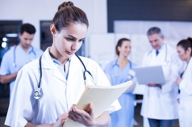 Doctora comprobando un informe médico y colegas parados detrás