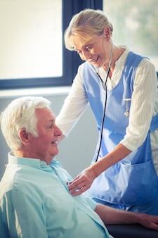 Doctora comprobando los latidos del corazón del hombre mayor