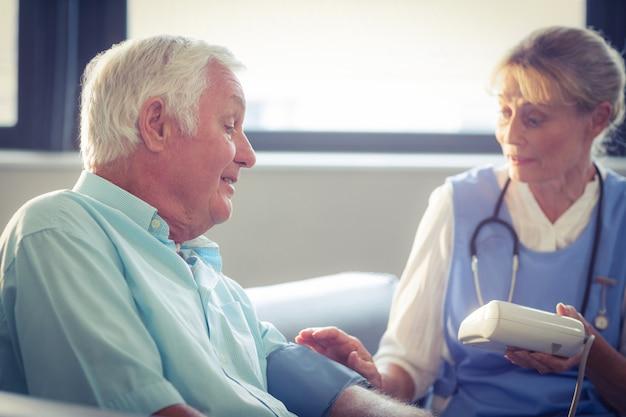 Doctora comprobando la presión arterial del hombre senior
