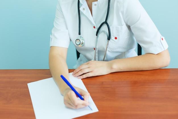 La doctora confiada con un estetoscopio se sienta a la mesa y escribe recomendaciones al paciente.