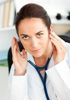 Doctora confidente usando un estetoscopio en su oficina