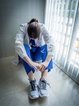 Doctora deprimida sentada en la desesperación en el pasillo de un hospital - concepto de salud y dolor