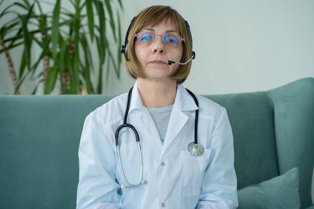 Doctora de edad avanzada con videollamada de auriculares hablando con una cámara web que consulta a un paciente virtual en línea