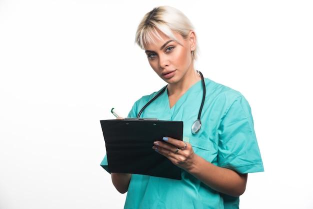Doctora escribiendo algo en el portapapeles con lápiz sobre superficie blanca