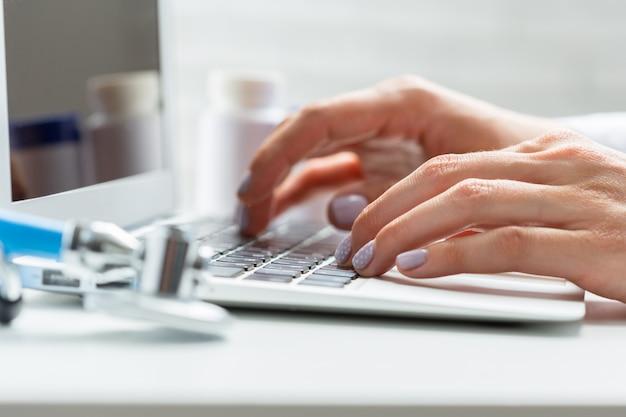 Doctora está escribiendo en computadora portátil