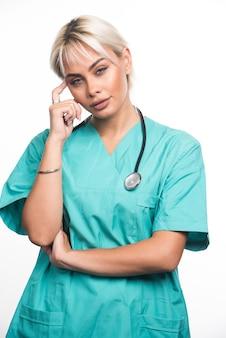 Doctora con estetoscopio apuntando con el dedo a la cabeza sobre la superficie blanca