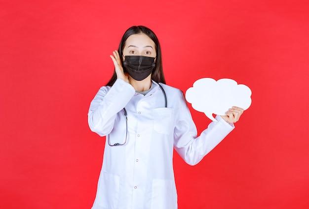 Doctora con estetoscopio y máscara negra sosteniendo un escritorio de información en blanco con forma de nube y abriendo la oreja para escuchar bien.