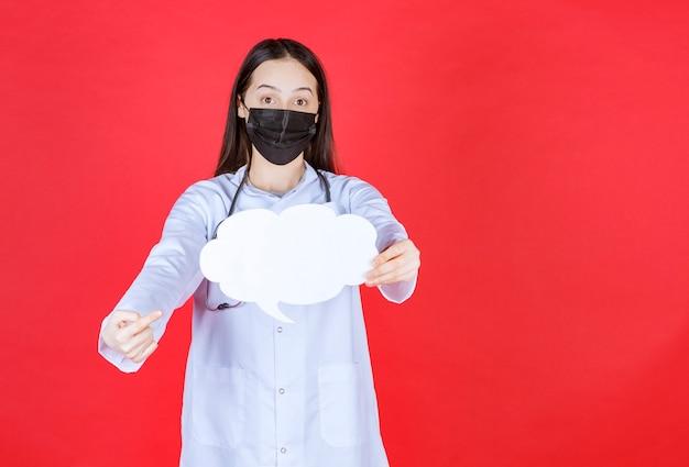 Doctora con estetoscopio y máscara negra sosteniendo un escritorio de información en blanco con forma de nube.