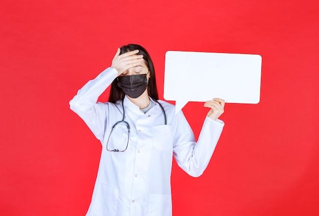 Doctora con estetoscopio y máscara negra sosteniendo un mostrador de información rectangular y sosteniendo la cabeza