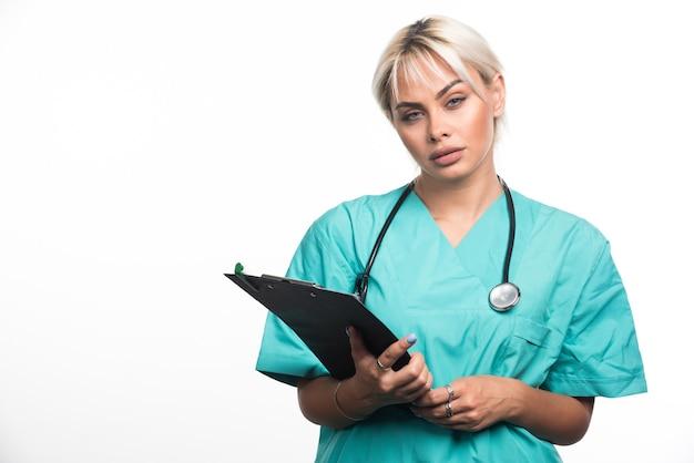 Doctora con estetoscopio sosteniendo portapapeles sobre superficie blanca