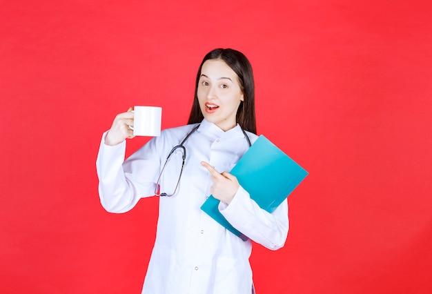 Doctora con estetoscopio sosteniendo una taza de bebida y una carpeta de historial del paciente.