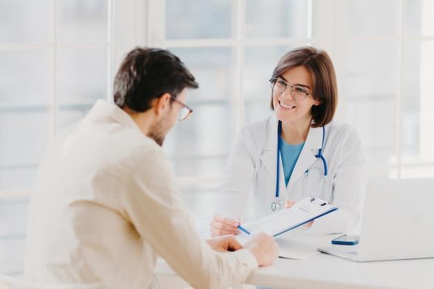 La doctora con estetoscopio sostiene una carpeta con la tarjeta médica personal del paciente, consulta al paciente que tiene problemas médicos, se sienta en la oficina del hospital, discute los resultados del chequeo médico, ofrece seguro