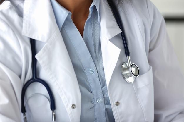Doctora con estetoscopio en uniforme blanco contra