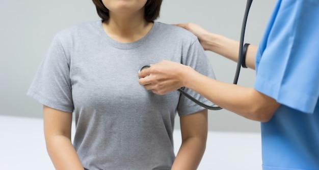 Doctora examina por palpación abdominal de paciente.