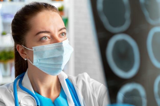 Doctora examina la resonancia magnética de la cabeza en el hospital