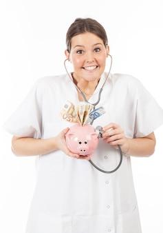 Doctora feliz con hucha llena de dinero