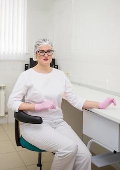 Una doctora con gafas y un uniforme blanco se sienta en una silla en la oficina de la clínica.
