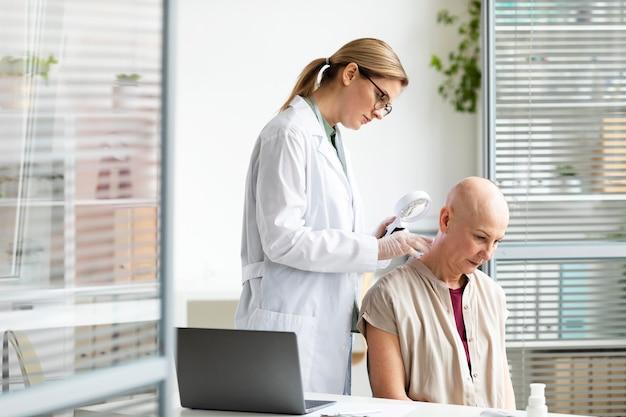 Doctora haciendo un chequeo a un paciente con cáncer de piel