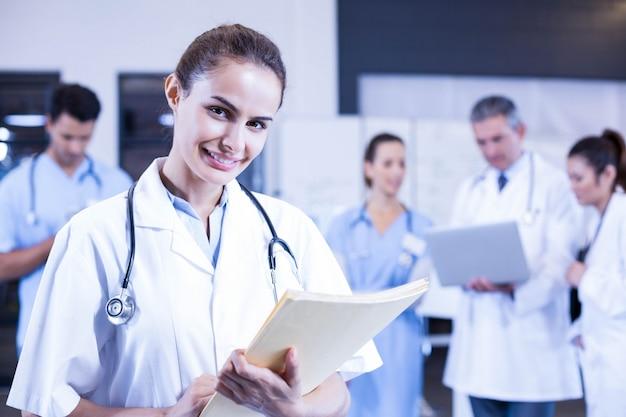 Doctora con informe médico y sonriendo mientras sus colegas de pie