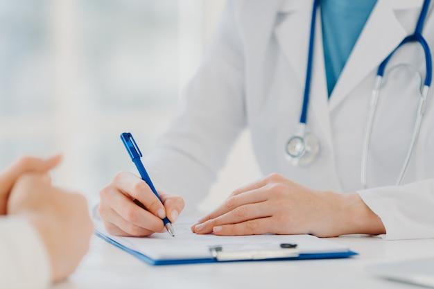 La doctora irreconocible escribe en el portapapeles, prescribe al paciente, registra los datos para su análisis, usa una bata blanca. de cerca, concéntrese en las manos. medicina, seguros, concepto de atención médica