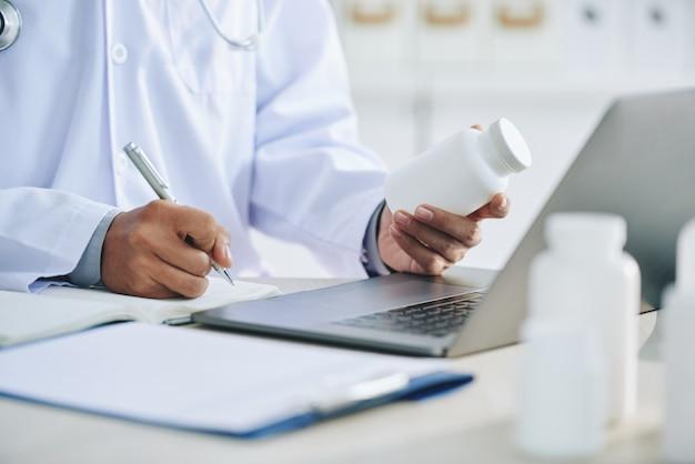 Doctora irreconocible con laptop sosteniendo medicamentos y escribiendo recetas