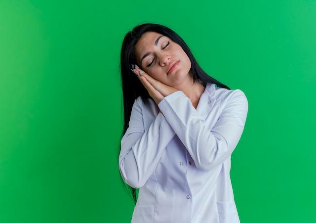 Doctora joven cansada vistiendo bata médica haciendo gesto de sueño con los ojos cerrados