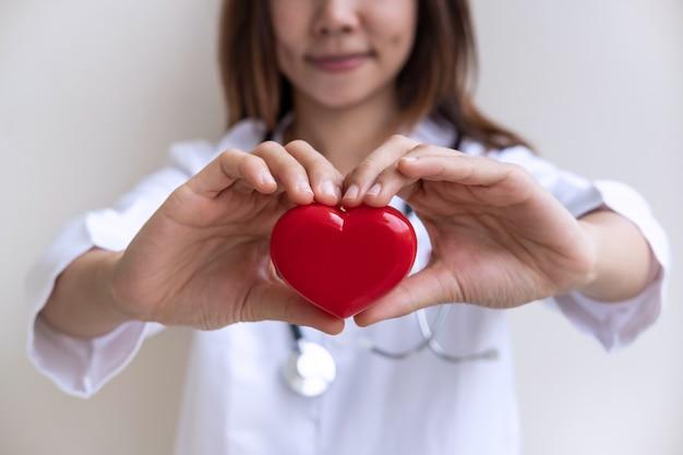 Doctora joven con el estetoscopio que lleva a cabo el corazón rojo, concepto sano del cuidado del cardiolog