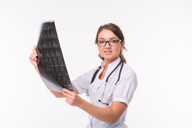 Doctora joven mirando la imagen de rayos x sobre fondo blanco. mri scan, resonancia magnética, concepto de radiología