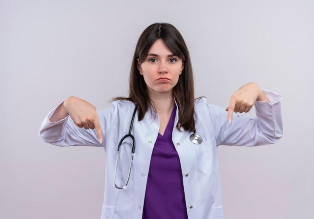 Doctora joven molesta en bata médica con estetoscopio apunta hacia abajo sobre fondo blanco aislado con espacio de copia