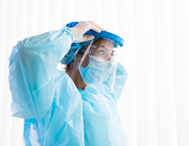 Doctora de lado poniéndose ropa protectora
