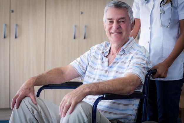 Doctora llevando senior hombre en silla de ruedas