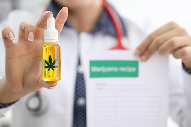 Doctora mano sostenga la botella con aceite de cbd