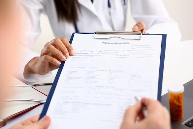 Doctora mano sostenga pluma de plata y mostrando un informe médico