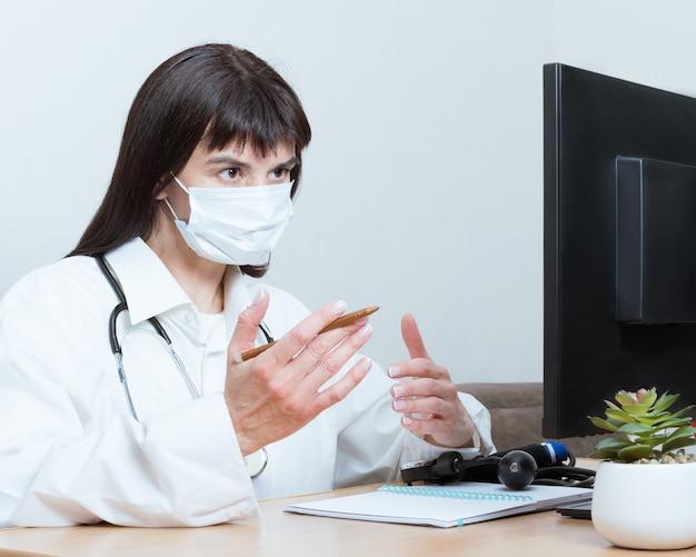Una doctora con una máscara médica hace una videollamada en línea, discute, gestos