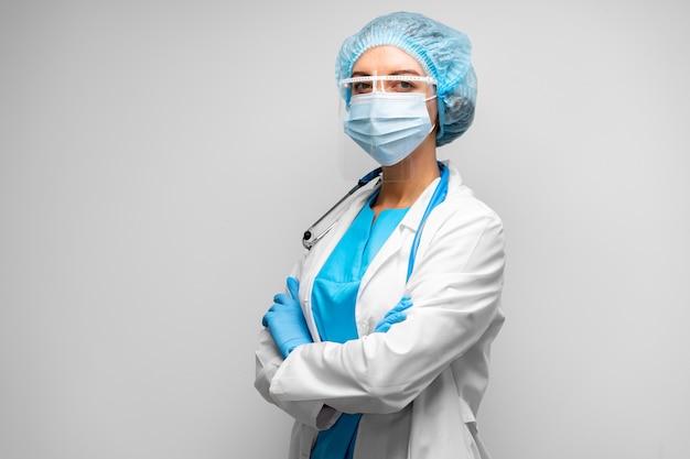 Doctora en máscara médica de pie contra el fondo gris, retrato