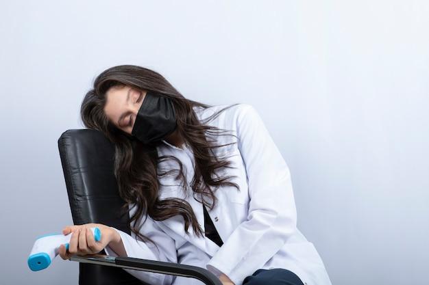 Doctora en máscara médica sosteniendo termómetro y durmiendo en una silla.