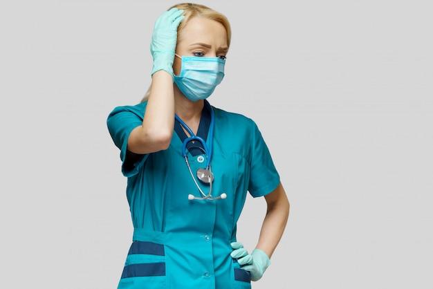 Doctora con máscara protectora y guantes de látex dolor de cabeza y estrés