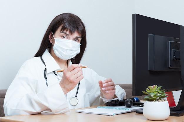 Una doctora con una máscara protectora médica lo está mirando mientras está sentada en una mesa en la oficina