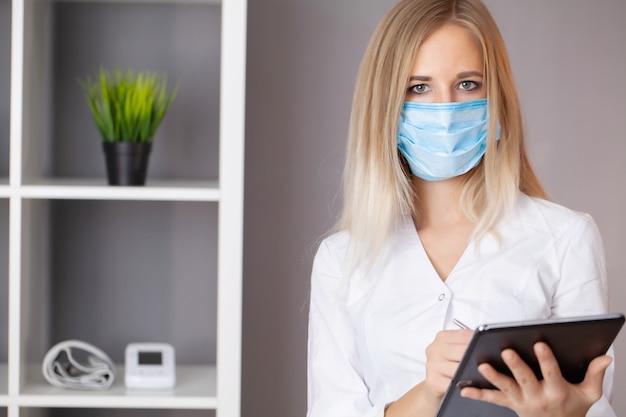 Doctora en máscara protectora trabajando en tableta en oficina