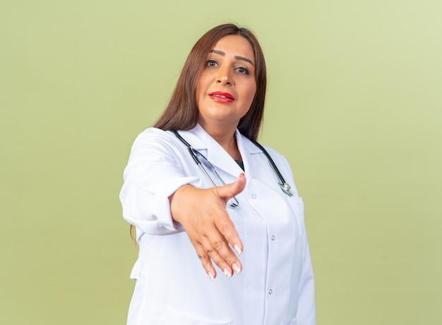 Doctora de mediana edad en bata blanca con estetoscopio mirando al frente sonriendo confiado ofreciendo mano haciendo gesto de saludo de pie sobre la pared verde
