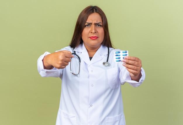 Doctora de mediana edad en bata blanca con estetoscopio sosteniendo blister con pastillas mirando al frente con cara seria mostrando puño frunciendo el ceño parado sobre pared verde