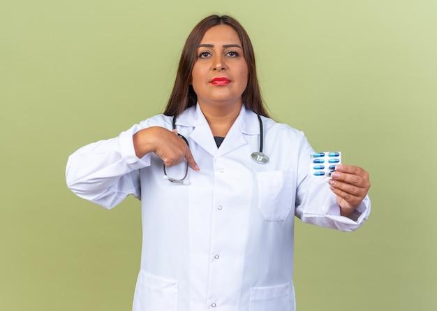 Doctora de mediana edad en bata blanca con estetoscopio sosteniendo blister con pastillas mirando con expresión de confianza apuntando a sí misma