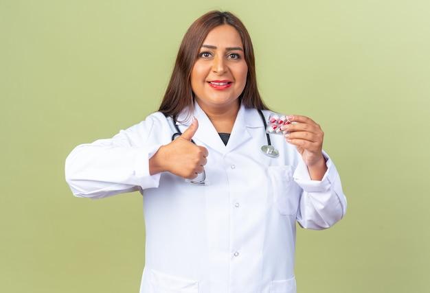 Doctora de mediana edad en bata blanca con estetoscopio sosteniendo blister con píldoras mostrando los pulgares para arriba sonriendo confiado de pie sobre la pared verde