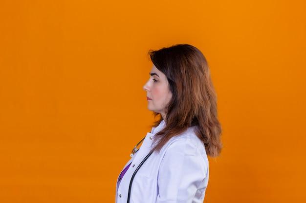 Doctora de mediana edad vistiendo bata blanca y con estetoscopio de pie hacia los lados con expresión seria de confianza en la cara sobre fondo naranja aislado