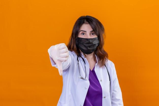 Doctora de mediana edad vistiendo bata blanca en máscara facial protectora negra y con estetoscopio mirando a cámara con rostro serio mostrando el pulgar hacia abajo de pie sobre fondo naranja