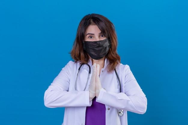 Doctora de mediana edad vistiendo bata blanca en máscara facial protectora negra y con estetoscopio tomados de la mano en gesto de oración namaste sintiéndose agradecido y feliz sobre fondo azul aislado