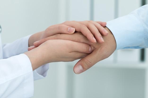 Doctora en medicina tranquilizando a su paciente. primer plano de las manos. concepto médico y sanitario.
